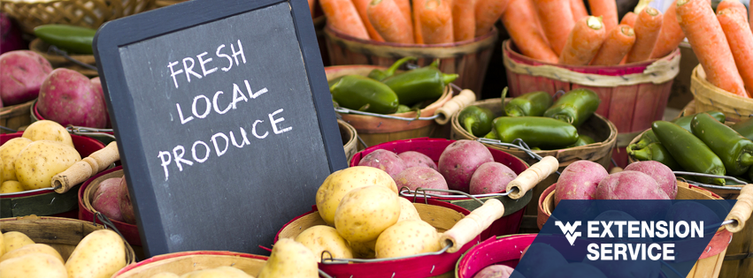 """Colorful produce in baskets with a chalkboard sign saying, """"fresh local produce."""""""